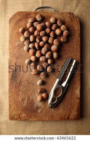 a lot of hazelnut on a wooden table with nutcracker - stock photo