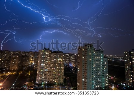 A lot of large lightning bolts in the sky above the city - over 20 lightnings - stock photo