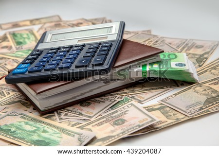 a lot of money and calculator are on the table. horizontal photo of money - stock photo