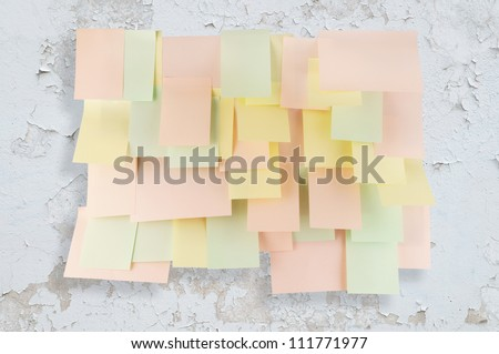 A lot of note papers on old white wall - stock photo