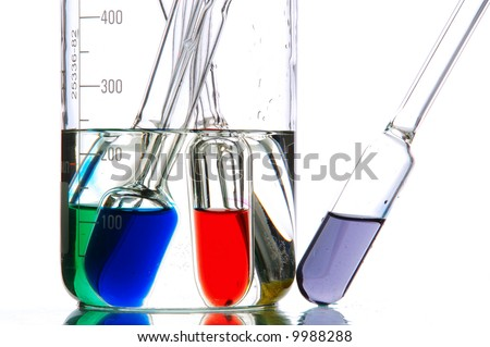 a lot of retorts with liquids of different colour, white background - stock photo
