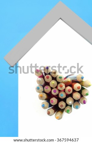 A Lot Of Sharped Colored Pencils Are Sticking Out From The Heart Shaped Window In The Home White Wall Isolated On Blue Background, Vertical Image - stock photo