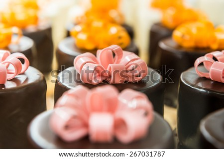a lot of small chocolate cakes with eatable bows - stock photo