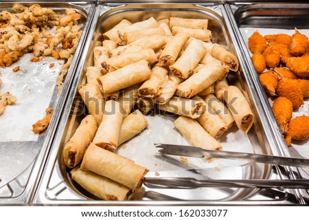 a lot of spring rolls in the food warmer of a self service restaurant - stock photo