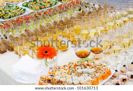 a lot of sushi rolls and drinks on buffet table, catering - stock photo