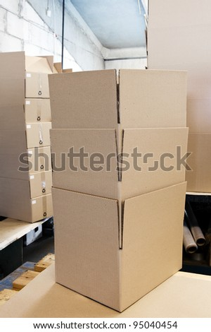 A lot of various cardboard boxes arranged up in stacks at an industrial distribution storage room - stock photo