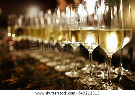 A lot of wine glasses with a cool delicious champagne or white wine at the bar. Alcohol background. - stock photo