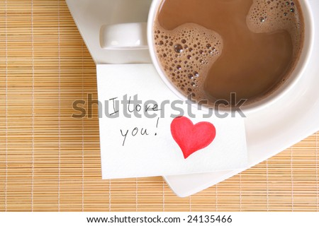 a love note with a cup of coffee on the table - stock photo