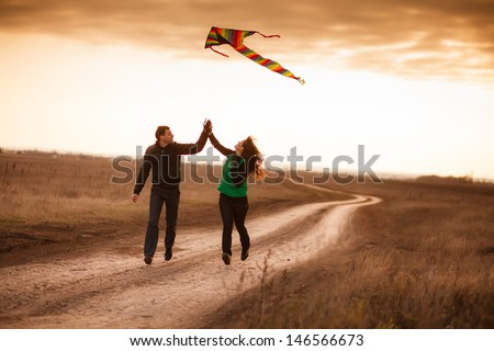 A love story. A man and a woman on autumn road running with a kite. Love and relationships. Autumn sunset. - stock photo