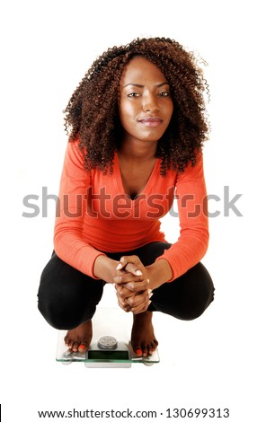 A lovely black teen girl crouching on a scale, looking into the camera, for white background in an orange sweater and black tights. - stock photo