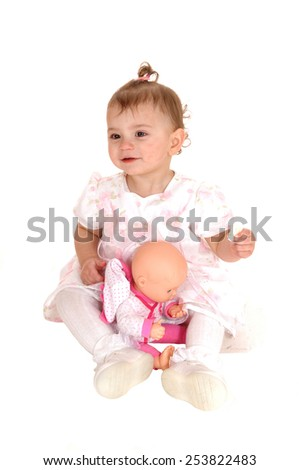 A lovely blond baby girl sitting on the floor holding her biscuits and playingwith her dolly, isolated for white background. - stock photo