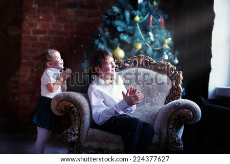 A lovely little girl and a young handsome boy looking through the window in front of the decorated Christmas tree and waiting for a miracle clapping their hands. - stock photo