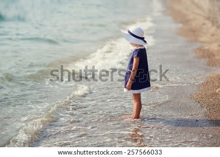 A lovely little girl in a dark blue dress and white hat walking barefoot on the waves along the beach on a summer sunny day. Holiday on a seashore. Sea. Ocean. - stock photo