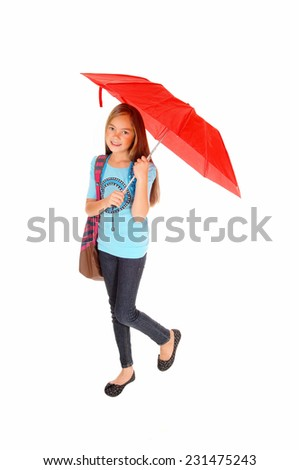 A lovely little girl in jeans standing isolated for white background holding a red umbrella and her backpack over her shoulder.  - stock photo