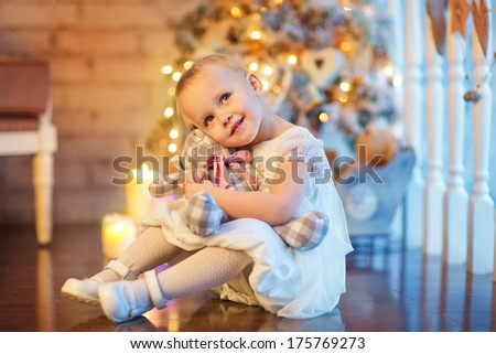 A lovely little 3 year old girl in a beautiful white dress sitting in front of the decorated Christmas tree and hugging her teddy bear - stock photo