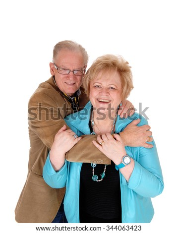 A lovely older couple embracing each other, the man standing behindhis wife, hugging, isolated for white background. - stock photo