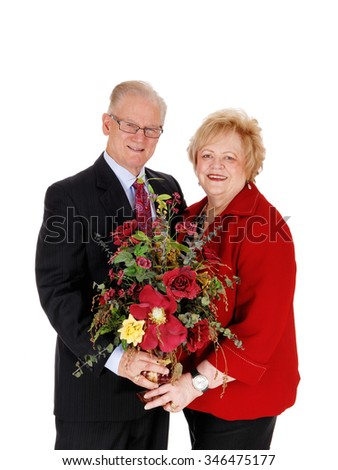 A lovely senior couple, full dressed up, holding silk flowers in there hand,isolated for white background. - stock photo