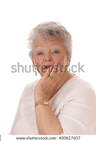 A lovely senior woman in her seventies holding her face in her hand andlooking surprised, isolated for white background. - stock photo