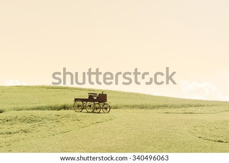 a lovely wooden cart on a graphic color of hills and sky for background - stock photo