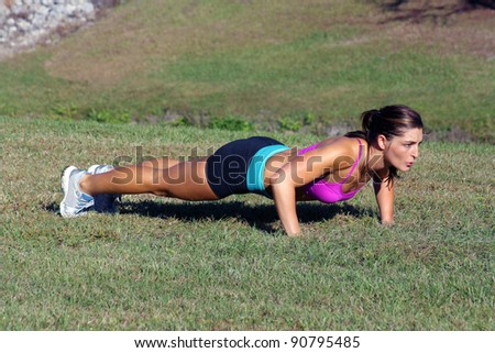 A lovely young athlete does pushups outdoors.  Generous copyspace. - stock photo