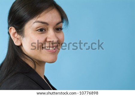 A lovely young woman with a friendly smile taken against a blue background with copy space. - stock photo