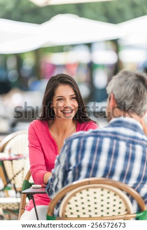A loving couple is sitting at an outside bar table in the city. They are facing each other. Focus on the woman. We can see the back of the grey hair man. - stock photo