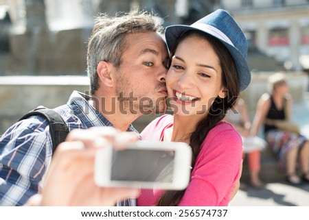 A loving couple is taking a selfie on their phone in the city center. The woman is wearing a hat. The grey hair man is kissing the woman on the cheek. They are looking at the camera. Focus on them. - stock photo