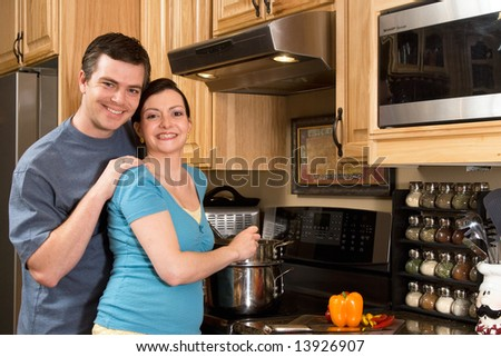 A loving couple standing in the kitchen cooking together.  Horizontally framed shot with both people looking at the camera. - stock photo