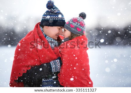 A loving couple walking in winter park. It's snowing, winter. Lovers covered a blanket, cuddling. Valentine's Day, Christmas. For young people wearing colorful scarves and hats. - stock photo