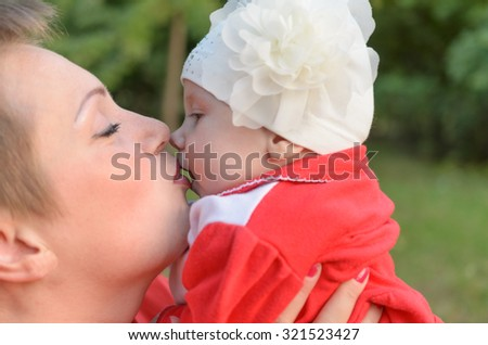 A loving mother tenderly kissing her child with affection. - stock photo