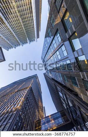 A low angle view of skyscrapers with dappled sunlight against a blue sky. - stock photo