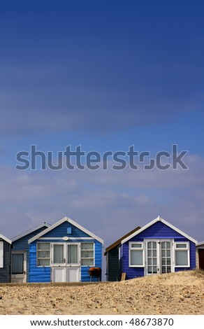 A low angled shot of a row of blue wooden beach huts set on a portrait format with room for copy above. Located in Christchurch, Hampshire UK. - stock photo