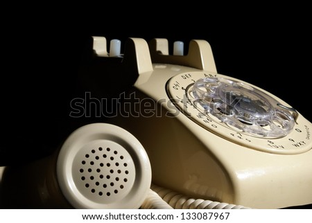 A low key shot of a rotary phone on hold. - stock photo