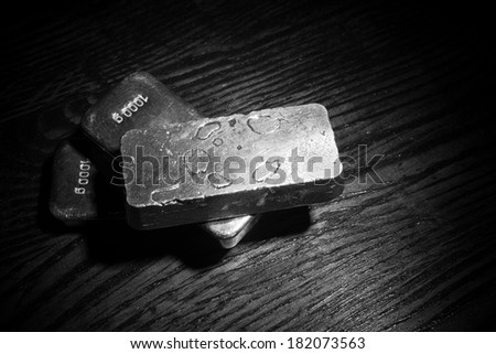 A low key still life with several  silver bars - stock photo