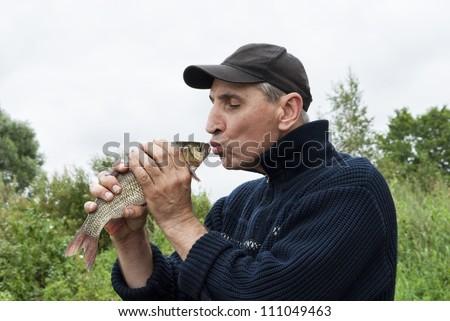A lucky fisherman kiss a chub - stock photo