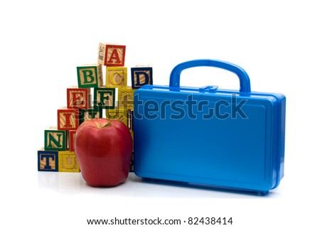 A lunch box and apple in front of color wooden blocks of the alphabet isolated over white, Schools Lunches - stock photo