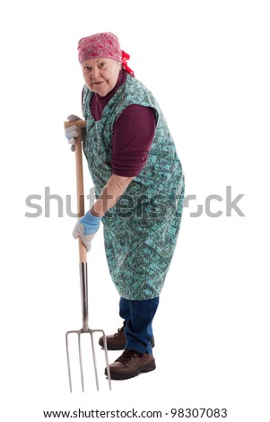A lusty female senior with pitchfork  looks to viewer 2 - stock photo