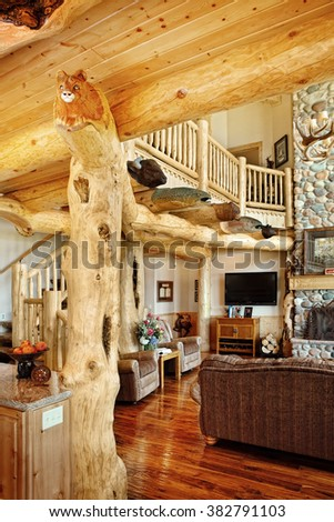 A luxurious living room, with comfortable furnishings and animal carvings, in a modern log cabin in the mountains. - stock photo