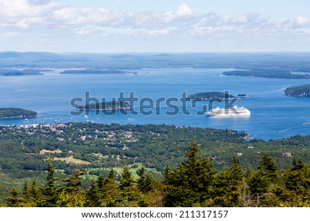 A luxury cruise ship docked in the ocean off the coast of Maine shot from evergreen covered hills - stock photo