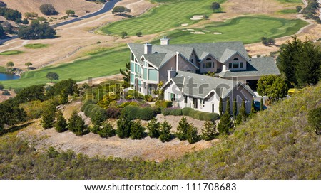 A luxury hillside home overlooking a golf course. - stock photo
