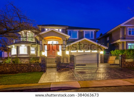 A luxury home behind the gates in suburbs at night, dusk time in Vancouver, Canada. - stock photo