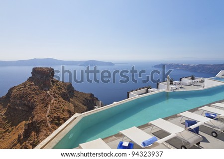 A luxury swimming pool situated in the town of imerovigli next to skaros on the greek island of santorini with a view of oia in the distance. - stock photo