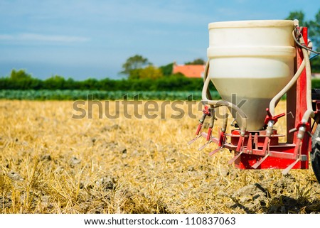 a machine is spreading the seeds on a piece of land - stock photo