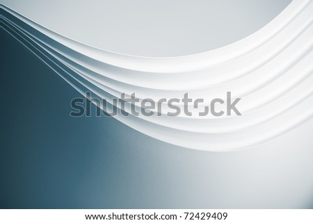 a macro, abstract image of several sheets of white paper arranged in a fluid, wave shape. - stock photo