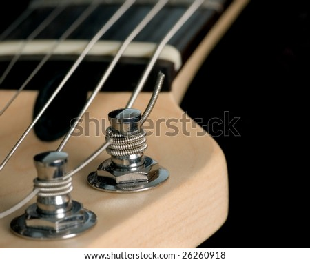 A macro closeup shot of an electric guitar head stock with string tuning pegs - stock photo