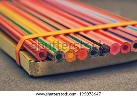 A macro photo of color pencils and a paper notebook - stock photo