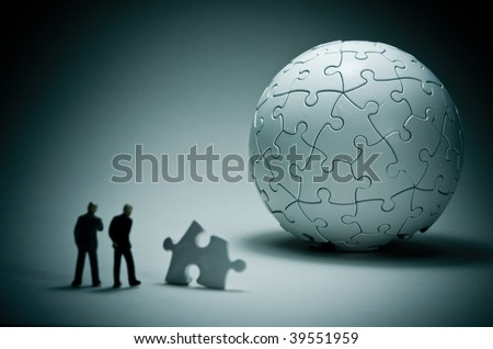 A macro shot of a globe puzzle with a couple of business people. - stock photo