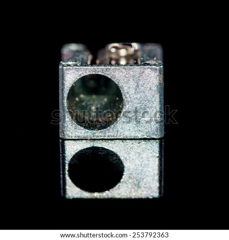 A macro shot of a pencil sharpener shot against a black background and showing a reflection. - stock photo