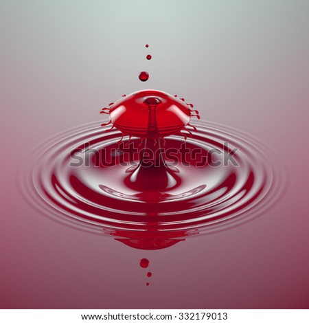A macro shot of a water drop collision in red color - stock photo