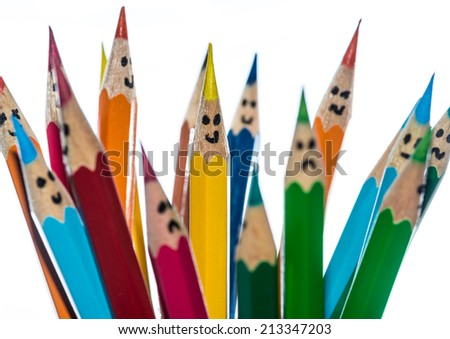 A macro shot of some coloured pencils with faces drawn on them. - stock photo